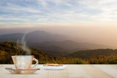 Горячий кофе с паром и печеньем на верхней части деревянного стола на запачканный Стоковая Фотография RF
