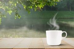 Горячий кофе с паром на верхней части деревянного стола на запачканной туманной предпосылке озера и леса Стоковое Фото