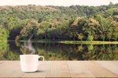 Горячий кофе с паром на винтажной верхней части деревянного стола на предпосылке озера и леса Стоковые Изображения