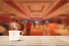 Горячий кофе с паром на винтажной верхней части деревянного стола на предпосылке лобби гостиницы Стоковые Фото