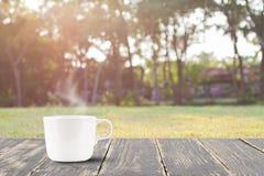 Горячий кофе с дымом на винтажной верхней части деревянного стола на запачканных луге и дереве Стоковое Изображение RF