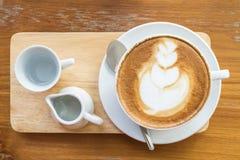 Горячий кофе latte в белой чашке на деревянном столе с космосом fo экземпляра Стоковая Фотография