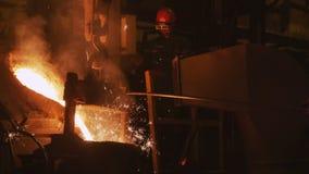 Горячий металл полил в форму и работника в стеклах в предпосылке видеоматериал