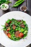 Горячий салат с зажаренной печенью, томатами вишни и смешанными зелеными цветами на темной деревянной предпосылке стоковая фотография