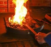 Горячий утюг в кузнице с огнем Стоковая Фотография RF