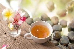 Горячий чай в белой чашке с цветками на деревянной воде b камня камешка Стоковые Изображения RF
