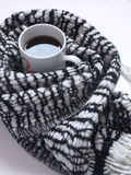 Горячий черный кофе с сделанным по образцу черно-белым шарфом на белом столе Плоское положение Взгляд сверху стоковые изображения