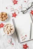 Горячий шоколад с зефирами и циннамоном, чистым пустым блокнотом, украшениями рождества на светлой предпосылке Inspirat рождества Стоковые Фотографии RF