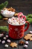 Горячий шоколад с зефирами и тросточками конфеты на темной деревянной предпосылке Стоковое фото RF