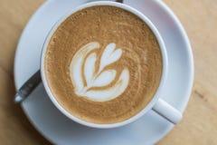 Горячий latte кофе с красивым искусством пены на стеклянном столе Крытый c Стоковое Фото