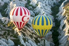 2 горячих воздушного шара плавают над ландшафтом около Goreme в Турции Стоковое Изображение
