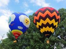 2 горячих воздушного шара перед деревьями в дне освещают Стоковое Фото
