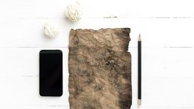 Горящая коричневая бумага и скомканная бумага с умным телефоном Стоковое фото RF