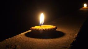 Горящая плоская свеча на ноче изолированная на темной предпосылке Стоковые Изображения
