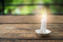 Горящая свеча в малой чашке на деревянном столе Стоковое Изображение