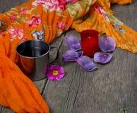 Горящая свеча, стальная кружка, оранжевый шарф Стоковая Фотография