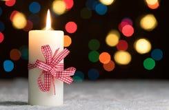 Горящая свеча с красным смычком, в снеге, с defocussed fairy светами, bokeh на заднем плане Стоковое Фото