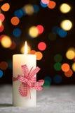Горящая свеча с красным смычком, в снеге, с defocussed fairy светами, bokeh на заднем плане Стоковая Фотография