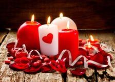 Горящие свечи в лепестках подняли на деревянную предпосылку Стоковая Фотография RF