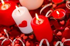 Горящие свечи в лепестках подняли на деревянную предпосылку Стоковая Фотография