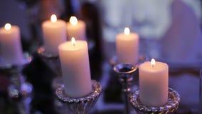 Горящие свечи в подсвечниках на таблице акции видеоматериалы