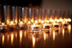 Горящие свечи в прозрачных стеклах, сияющем поле, отражении Настроение, релаксация, молитва и комфорт Стоковые Изображения RF