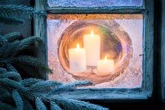 Горящие свечи для рождества в замороженном окне на кануне Стоковые Фотографии RF