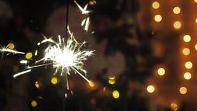 Горящий бенгальский огонь на предпосылке светов и гирлянд рождественской елки narazeni сбоку акции видеоматериалы