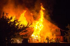 Горящий деревянный дом на ноче Яркие оранжевые пламена и плотный sm стоковые фото