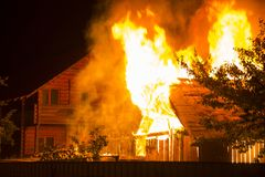 Горящий деревянный дом на ноче Яркие оранжевые пламена и плотный sm стоковая фотография rf
