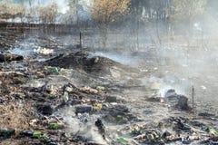 Горящий отброс на противозаконном ненужном dumo около земли черноты леса и тяжелое старье курят Концепция отавы загрязнения окруж стоковые изображения
