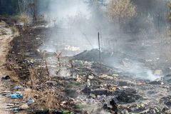 Горящий отброс на противозаконном ненужном dumo около земли черноты леса и тяжелое старье курят Концепция отавы загрязнения окруж стоковая фотография rf