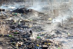 Горящий отброс на противозаконном ненужном dumo около земли черноты леса и тяжелое старье курят Концепция отавы загрязнения окруж стоковые фотографии rf