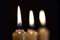 3 горящих свечи воска на черной предпосылке Стоковое Фото