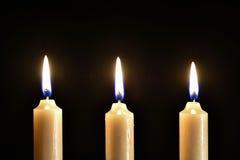 3 горящих свечи воска на черной предпосылке Стоковая Фотография