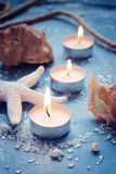 3 горящих свечи в ряд на предпосылке моря возражают, олово Стоковое Изображение RF