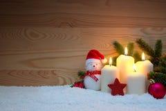 4 горящих свечи и снеговик пришествия с красными украшениями рождества Стоковое Фото