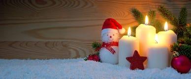 4 горящих свечи и снеговик пришествия с красными украшениями рождества Стоковые Фото