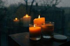 3 горящих свечи на таблице, уютный дождливый день дом Стоковое фото RF