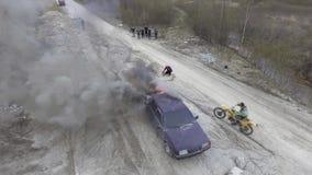 Горя автомобиль в дезертированных полях пыли с двигая motorbikers и наблюдая людьми сток-видео
