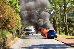 Горя автомобиль на дороге стоковое изображение