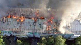 Горя крыша жилого многоэтажного здания, облака дыма от огня пожарные тушат огонь top сток-видео