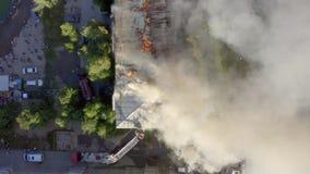 Горя крыша жилого многоэтажного здания, облака дыма от огня пожарные тушат огонь top видеоматериал