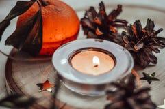 Горя свеча окруженная конусами и tangerines сосны стоковая фотография rf