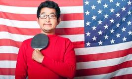 Гордый азиатский человек держа затвор настольного тенниса против флага США Стоковые Фотографии RF