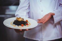 Гордый шеф-повар держа плиту спагетти чернил кальмара Стоковые Фотографии RF