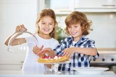 2 гордых дет с их первым домодельным fruitcake Стоковые Фотографии RF
