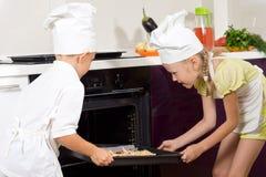 2 гордых маленького ребенка кладя пиццу в печь Стоковая Фотография