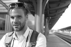 Госпож концепция поезда и путешествовать Турист с усмехаясь стороной и рюкзаком Молодой человек на платформе Стоковые Изображения