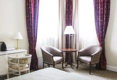 Гостиничный номер в спокойных цветах, зоне усаживания, креслах и окне Стоковое Фото